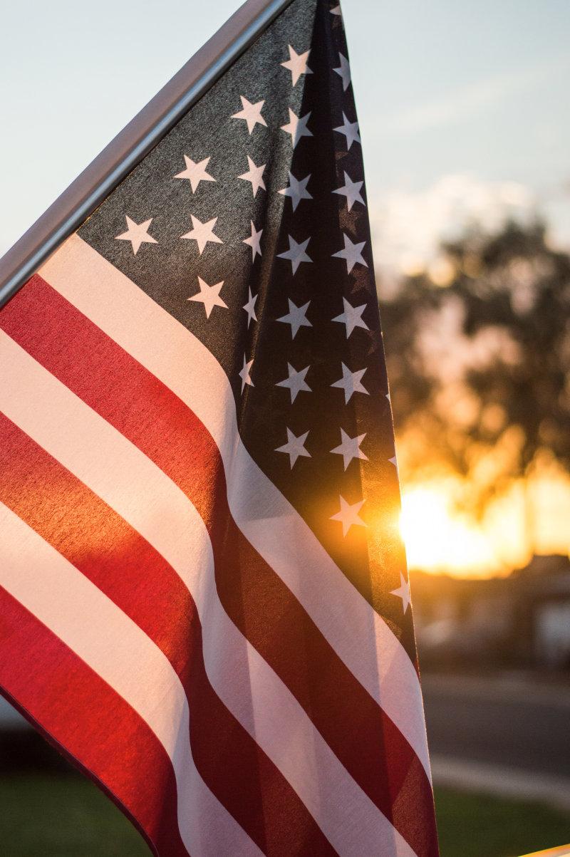 American Flag with sun on horizon